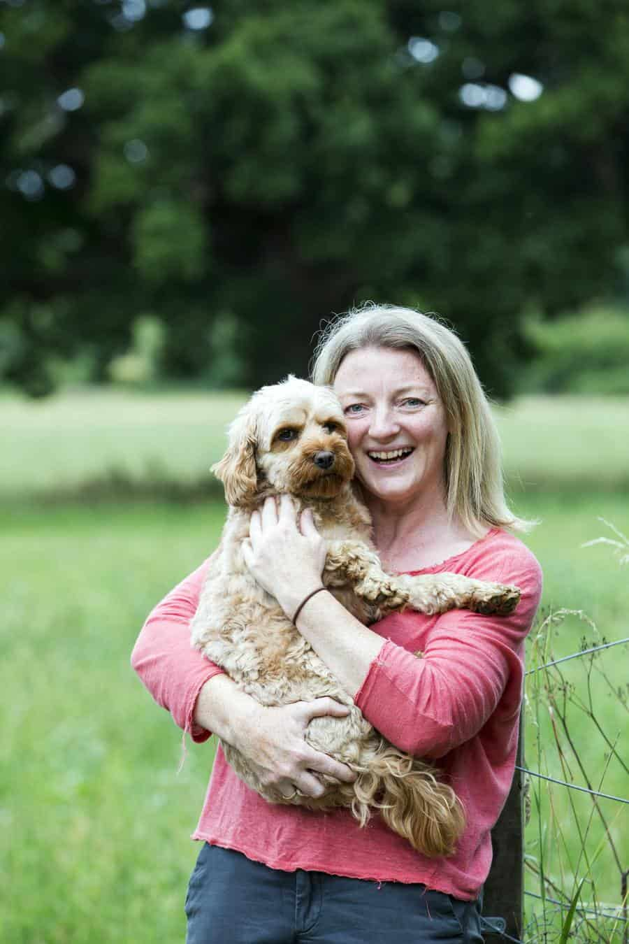 Portrait of smiling woman holding fawn coated young Cavapoo.